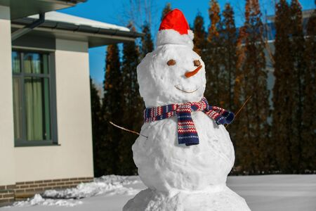 Winter time. Snowman on a yard near house no people Archivio Fotografico - 133691237