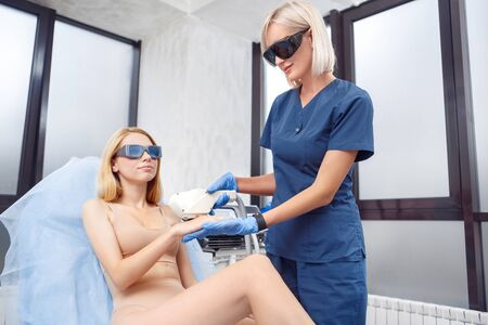 Cosmetology Service. Young woman at beauty clinic lying on medical bed in safety goggles smiling relaxed while doctor using photorejuvenation laser on hand removing vascular lesion