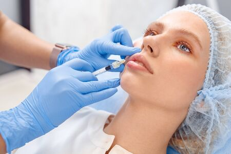 Cosmetology Service. Young patient in hair cap at beauty clinic close-up lying while doctor making injections of hyaluronic acid into lips Stock Photo