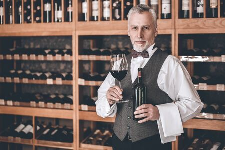 Sommelier Concept. Senior man standing with bottle and glass of wine smiling confident