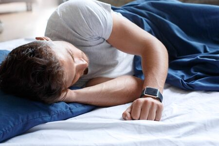 Bedtime. Guy sleeping on bed peaceful with smartwatch
