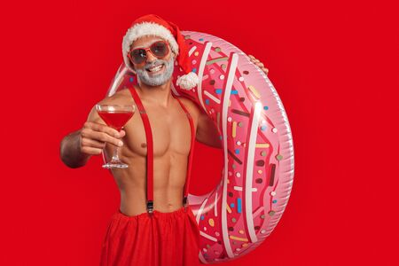 Adult sexy Santa Claus standing with inflatable ring for pool and cocktail in hands