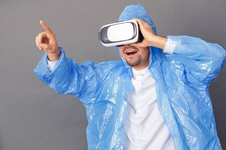 Entertainment. Young man in raincoat and virtual reality headset studio standing isolated on grey playing game smiling impressed Standard-Bild - 133691362