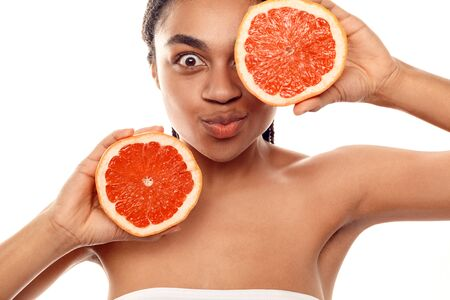 Beauty Concept. Young african woman isolated on white covering eye with grapefruit pouting lips silly close-up