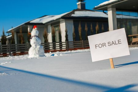 Winter time. House for sale board on a yard no people Archivio Fotografico - 133691815