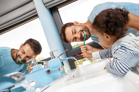 Father brushing teeth in bathroom with daughter