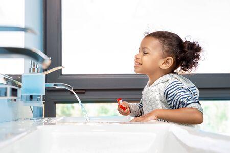 Little child girl brushing teeth in bathroom 版權商用圖片