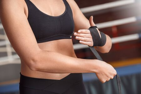 Boxing. Woman boxer putting bandage around wrist near ring close-up 版權商用圖片