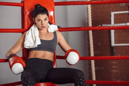 Boxing. Woman boxer with towel on neck in gloves sitting in the corner of ring looking forward curious