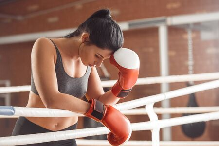 Boxing. Woman boxer in gloves leaning on rope on ring touchign head tired
