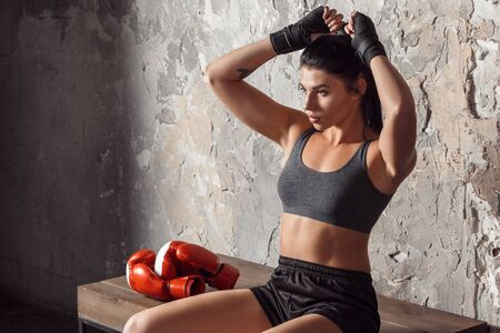 Boxing. Woman boxer sitting on bench making ponytail thoughtful