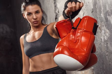 Boxing. Woman boxer showing gloves to camera close-up standing isolated on wall blurred