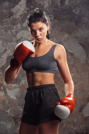 Boxing. Woman boxer in gloves standing isolated on wall serious