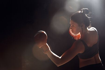 Boxing. Woman boxer in gloves exercise on dark ring standing protective side view 版權商用圖片