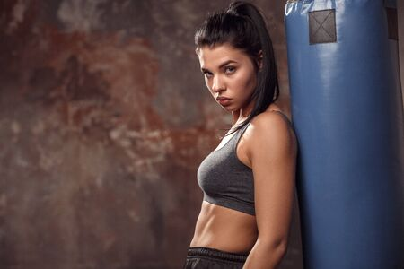 Boxing. Woman boxer leaning on punching bag looking camera serious