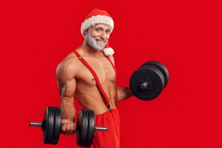 Christmas Freestyle. Young Santa Claus bare muscular upper body in hat standing isolated on red exercise with dumbbells smiling happy