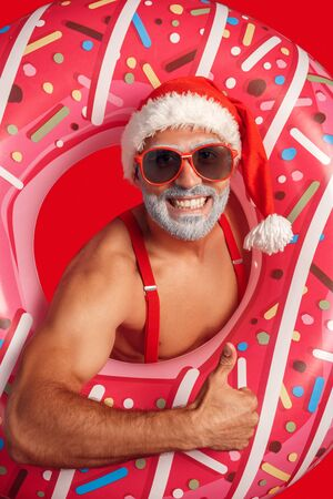 Christmas Freestyle. Young Santa Claus bare muscular upper body in hat and sunglasses standing isolated on red in swim ring thumb up smiling cheerful close-up 写真素材
