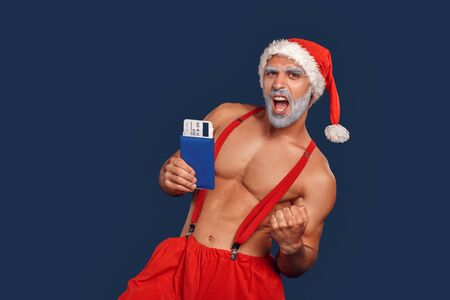 Christmas Freestyle. Young Santa Claus bare muscular upper body in hat standing isolated on blue with passport and ticket making fist successful