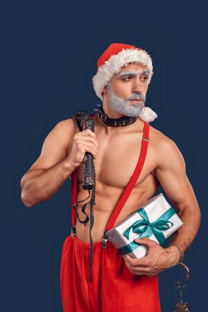 Christmas Freestyle. Young Santa Claus bare muscular upper body in hat and dog collar standing isolated on blue holding handcuffs whip and present looking aside playful