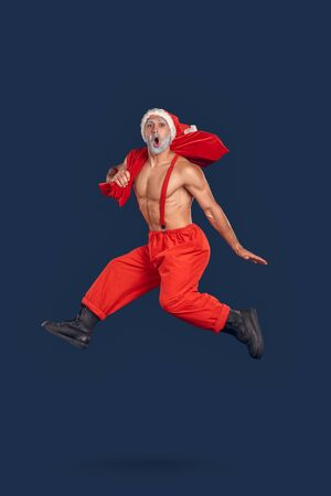 Christmas Freestyle. Young Santa Claus bare muscular upper body in hat jumping isolated on blue with gift bag on shoulder shouting excited