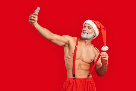 Christmas Freestyle. Young bearded Santa Claus bare muscular upper body in hat standing isolated on red taking selfie on phone holding suspenders smiling perfect