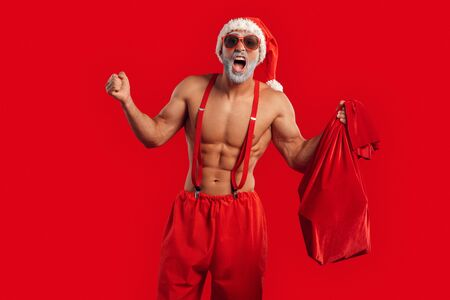 Christmas Freestyle. Young bearded Santa Claus bare muscular upper body in hat and sunglasses standing isolated on red with gift bag hands aside shouting excited