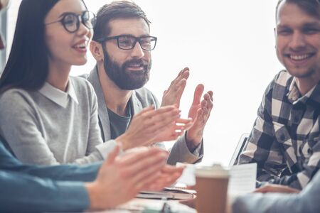 Startupers working together at office having business meeting clapping satisfied close-up