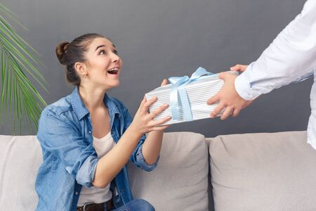 Holiday Concept. Young couple man standing giving gift to woman sitting on sofa smiling surprised studio isolated on grey close-up Stock Photo