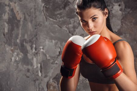 Boxing. Woman boxer in gloves standing isolated on wall ready to kick confident 版權商用圖片