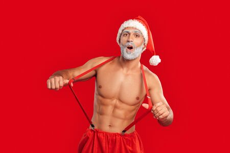 Handsome Santa Claus holding hands on suspenders