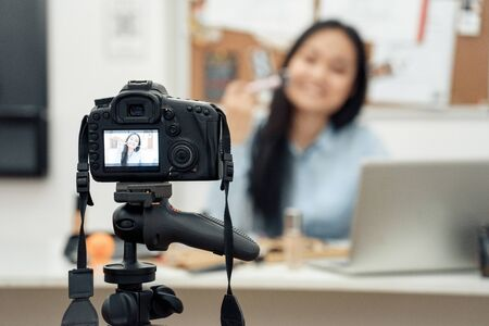 Young adult asian girl recording video on camera