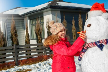 Winter vacation. Girl standing outdoors near house making snowman nose with carrot smiling happy close-up