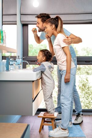 Mixed Race Family. Mother father and daughter at bathroom brushing teeth joyful side view
