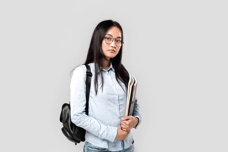 Young adult asian student girl standing in studio with backpack and copybooks