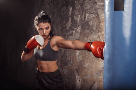 Boxing. Woman boxer in gloves exercise with punching bag practising kick side view Stock Photo