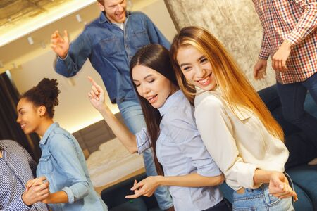Group of friends having party indoors fun together girls dancing passionate