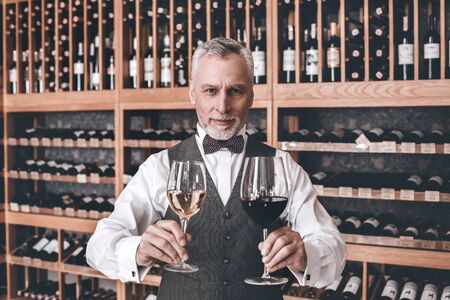 Sommelier Concept. Senior man standing with glasses of red and white wine smiling friendly