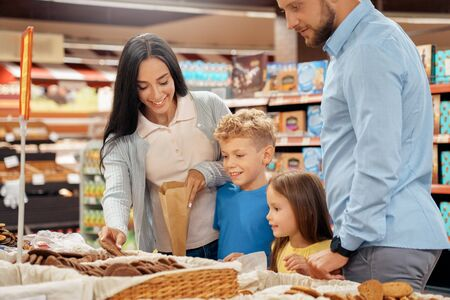 Parents choosing cookies with kids in supermarket