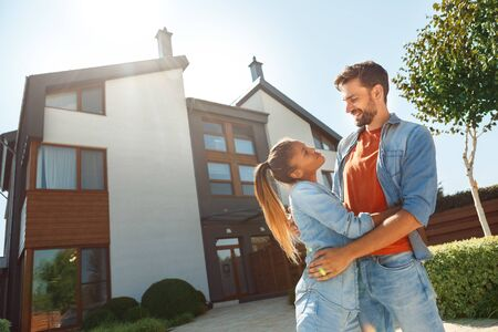 Young adult woman and man standing against new house together