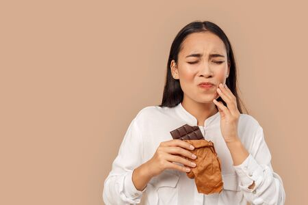 Freestyle. Young woman in shirt standing isolated on bage eating chocolate bar closed eyes having teeth ache