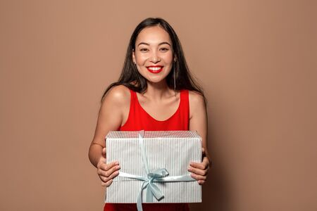 Freestyle. Young girl in dress standing isolated on brown with present box smiling cheerful