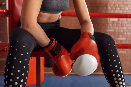 Boxing. Woman boxer in gloves sitting in the corner of ring close-up