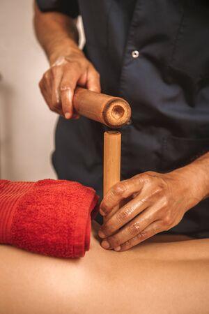 Alternative Medicine. Woman lying while therapist doing bamboo massage close-up