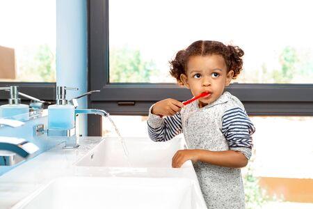 Mixed Race Child. Little girl brushing teeth looking aside pensive Stock fotó