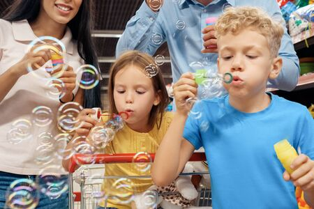 Parents and their little childrens blowing soap bubbles in supermarket