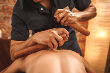 Alternative medicine and spa salon woman lying on medical bed while therapist doing back and shoulder massage using hollow bamboo canes close-up