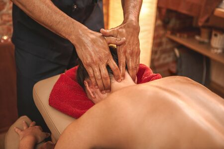 Alternative medicine salon woman lying face down on medical bed while therapist doing head and neck massage pressing concentrated for stress relief