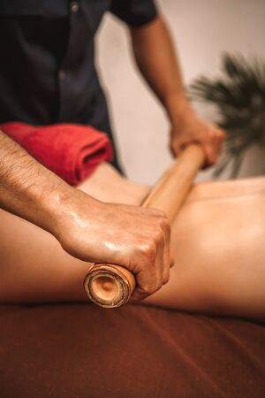Alternative medicine and spa salon woman lying on medical bed while therapist doing massage using hollow bamboo cane rolling on back close-up vertical