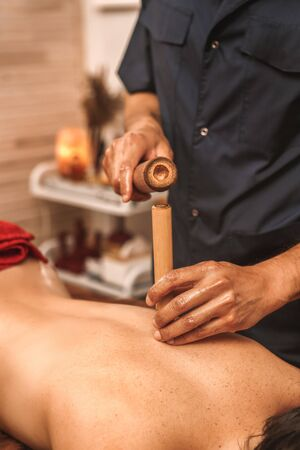 Alternative medicine and spa salon woman lying on medical bed while therapist doing back massage using hollow bamboo canes close-up