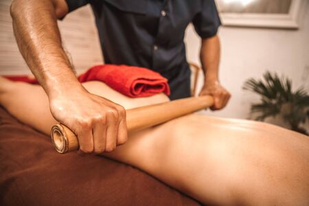 Alternative medicine and spa salon woman lying on medical bed while therapist doing massage using hollow bamboo cane rolling on back close-up concentrated